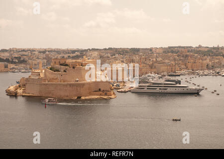 View over the Grand Harbour and Fort St. Angelo with Vittoriosa Yacht Marina from Upper Barrakka Gardens in Valletta, Malta. - Stock Photo