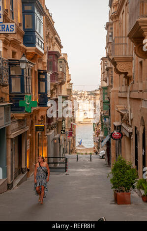 A view down San Gwann Street (Triq San Gwann). It is a typical narrow side street of shops and residences in central Valletta, the walled capital of M - Stock Photo