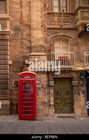 Traditional English red phone box outside a Baroque building in Merchants Street in Valletta, Malta. - Stock Photo