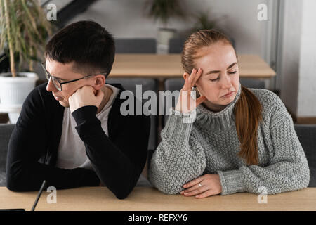 Angry unhappy young couple ignoring not looking at each other after family fight or quarrel, upset thoughtful spouses avoiding talk, sitting silently on couch, having relationship troubles - Stock Photo