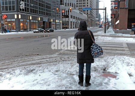 Cleveland, Ohio, USA, 21st January, 2019.  Cold weather grips the midwest as winter storm Harper leaves but followed by the coldest temperatures of the winter season.  A woman stands at East 9th Street and Superior Avenue during morning rush hour where across the street the temperature reads 11f.  Credit: Mark Kanning/Alamy Live News. - Stock Photo