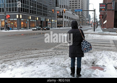 Cleveland, Ohio, USA, 21st January, 2018.  A woman waits to cross Superior Avenue in downtown Cleveland, Ohio, USA while across from her the temperature reads -12c on the outdoor marquee.  Credit: Mark Kanning/Alamy Live News. - Stock Photo