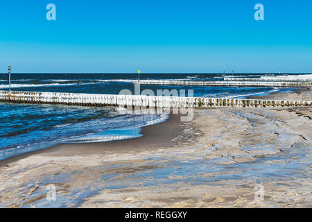 Beach of the Baltic Sea at Kolberg in winter. Ice covered Groynes are in the water, Kolobrzeg, West Pomeranian, Poland, Europe - Stock Photo