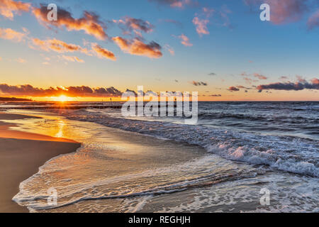 Sunset at the beach of the Baltic Sea in Kolobrzeg, Western Pomerania, Poland, Europe - Stock Photo