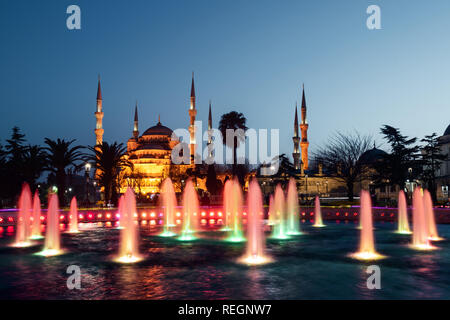 Fountain on Sultanahmet area in evening time. Multicolored streams against the background of the Blue mosque. Located place: Istambul, Turkey - Stock Photo