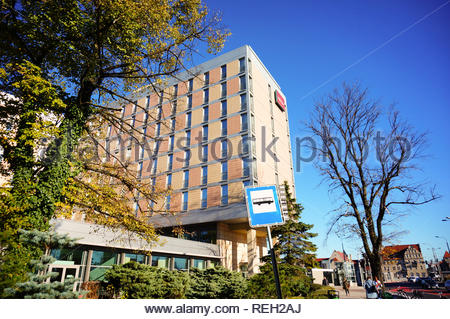 Poznan, Poland - October 31, 2018: High Mercure Hotel building on the Roosevelta street. Tree and bus stop sign in the foreground. - Stock Photo