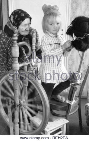 The grandmother is teaching her granddaughter to spin woolen thread. Old woman knew how to spin wool thead using ancient wooden spininng wheel. All the time she showed this process to her dranddauther. And I had a chance to make a photo of these lessons. - Stock Photo