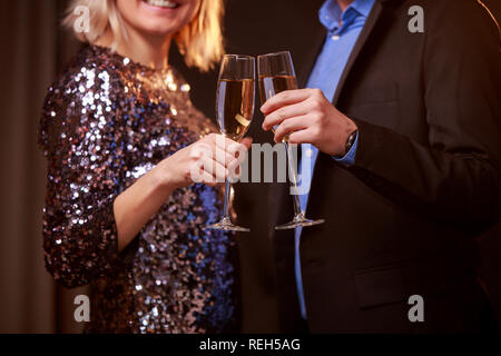 Photo of blonde woman in brilliant dress and men with wine glasses with champagne on black background - Stock Photo