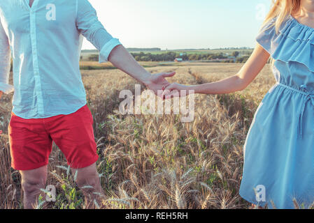 A guy with a girl in summer goes on a wheat field, holding each other hands. Close-up summer in the countryside. The concept of happy relationships and strong love in marriage. - Stock Photo