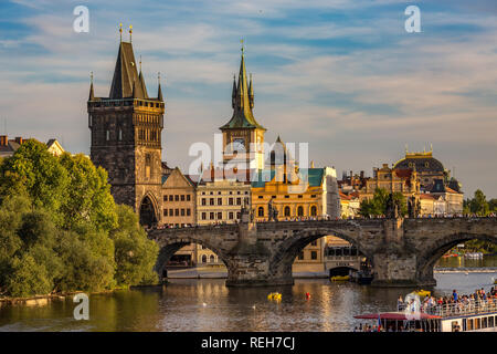 PRAGUE, CZECH REPUBLIC - AUGUST 27, 2015: Tour boats sail and pass under the medieval stone Charles Bridge on Vltava River, Prague, Czech Republic - Stock Photo