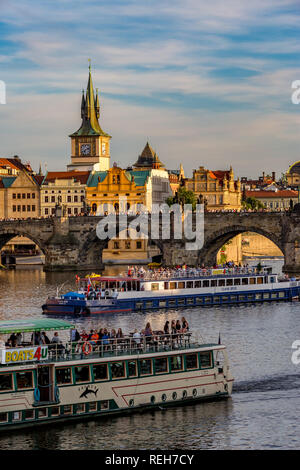 PRAGUE, CZECH REPUBLIC - AUGUST 27, 2015: Tour boats sail and pass under the medieval stone Charles Bridge on Vltava River, Prague, Czech Republic in  - Stock Photo