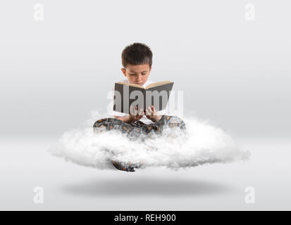 Young boy levitiating on cloud while reading a book. - Stock Photo