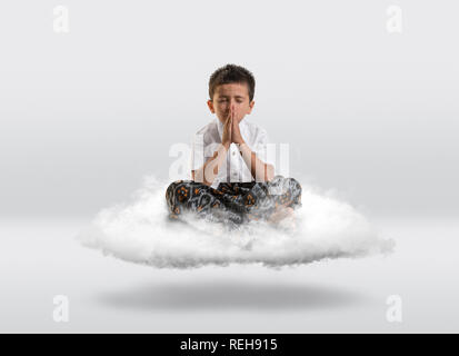 Young boy levitiating on a cloud with copy space all around. - Stock Photo