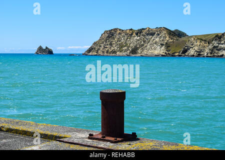 The post at the end of the long walkway along the wharf in Tolaga Bay, New Zealand - Stock Photo
