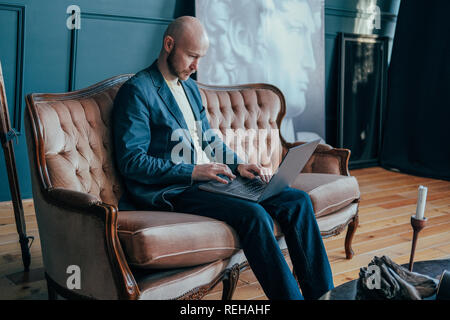 Attractive adult successful surprised bald man with beard in suit working at laptop on his rich cabinet - Stock Photo