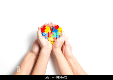 Adult and child hands holding colorful heart on white background. World autism awareness day concept. - Stock Photo