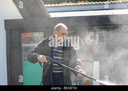 Senior man cleaning his grill ,using high pressure water. - Stock Photo