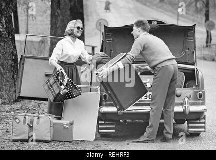 Couple in the 1960s. A young couple are packing the trunk of their car with luggage and camping gear for a car vacation. A practical folding table is also packed. She is dressed in a typical 1950s manor with a white shirt, wide skirt, sunglasses and her hair in a scarf. Sweden 1957 - Stock Photo