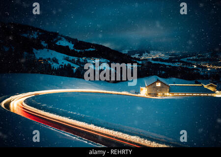 Long exposed night photography of cars driving through a snowy mountain road in the alps of Austria. - Stock Photo