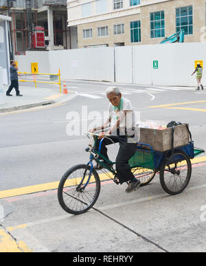 SINGAPORE - FEBRUARY 18, 2017: Man riding a tricycle on the road in Singapore. Singapore is the major financial center in Asia - Stock Photo
