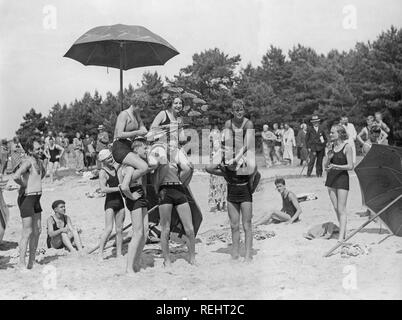 1920s beach party. A group of teenagers play on the beach outside Visby, a town on the Gotland island. - Stock Photo