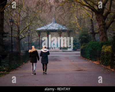 Battersea Park's ornate Victorian bandstand in golden hour, with two women walking towards it - Stock Photo