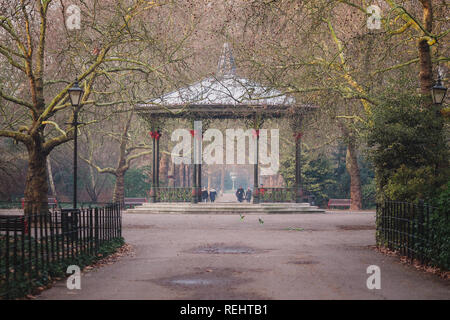 Battersea Park's Victorian bandstand during morning golden hour. In front of the bandstand you can see some of the green parakeets which live in the p - Stock Photo