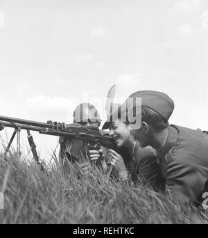 The Regiment's day in the 1940s. A fashionable looking lady is behind a machinegun together with two soldiers. She aims carefully, closing one eye. Sweden 1942 Photo Kristoffersson C20-3 - Stock Photo