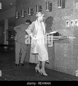 Woman in the 1950s. A young couple in an airport, is using the telephone. She is fashionable dressed in a typical 1950s two piece dress with matching skirt and jacket, with a lightweight coat. The gloves, handbag and shoes are made to match. Sweden 1958. Photo Kristoffersson Ref CB15-7 - Stock Photo