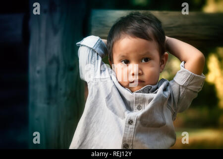 Young toddler boy that looks troubled, worried, or expressing anti social behavior while holding his head with his arms. - Stock Photo