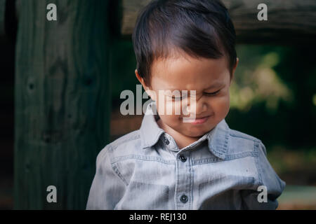 A little boy crying or throwing a temper tantrum with a frowned face, associated with emotional distress. - Stock Photo