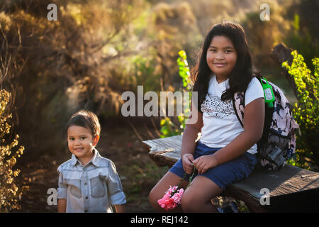 A boy and his older sister are sitting down, taking a break during a hike or field trip while the sun is setting. - Stock Photo