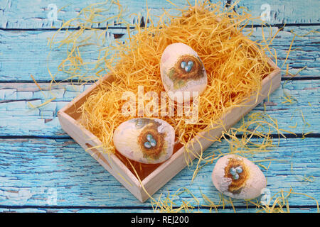 Decorative eggs for coloring on a blue wooden background. Easter. - Stock Photo