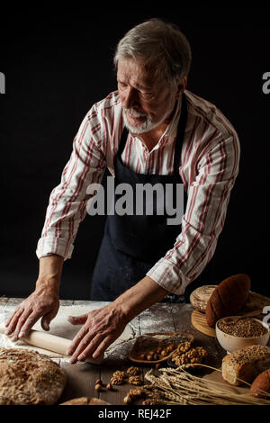 Experienced Baker Man preparing dough for homemade bread in the kitchen. - Stock Photo