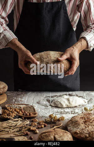 Unrecognizable baker holds freshly baked rustic organic loaf of bread in hand