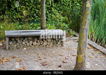 Ornate garden bench doubling as a log store - Stock Photo