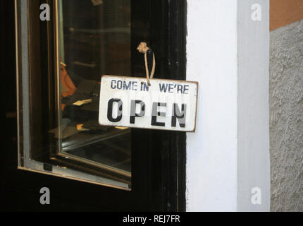 Come in we're open sign on a shop's door - Stock Photo