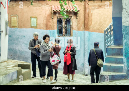Chefchaouen, Morocco - November 4, 2018: Oriental tourists visiting in Chefchaouen, Morocco, looking at their mobile phones - Stock Photo