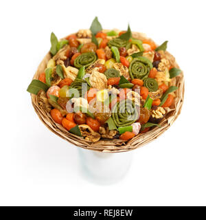 Original gift in the form of a bouquet of various tasty dried fruits on a white background. Side view - Stock Photo