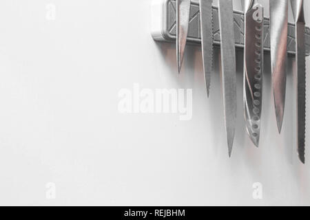 Knives on magnetic wall support in a kitchen on white wall, space for text - Stock Photo
