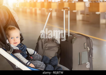 Cute funny caucasian baby boy sitting in stroller near luggage at airport terminal. Child sin carriage with suitcasese near check-in desk counter. Travelling with small children concept - Stock Photo