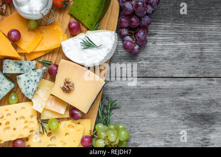 various types of cheese on cutting board with grape and nuts over rustic wooden table, top view with copy space - Stock Photo