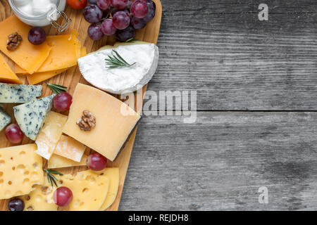 Assorted cheeses on wooden board plate served with walnuts, grapes and rosemary on rustic wood background, top view with copy space - Stock Photo