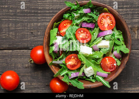 Fresh salad with rucola, tomatoes cherry, feta cheese and red onion in a bowl on rustic wooden table. top view with copy space - Stock Photo