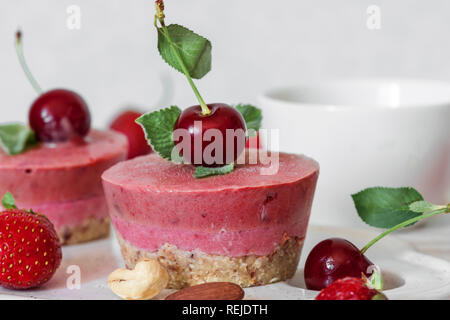 healthy breakfast. homemade strawberry and cherry cheesecakes with fresh berries, mint, nuts and coffee cup. vegan food concept