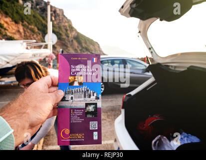 Port de Valldemosa, Palma de Malloca, Spain - May 10, 2018: Man holding pov the touristic guide of the Santa Maria of Palma Cathedral in the parking near sea - Stock Photo
