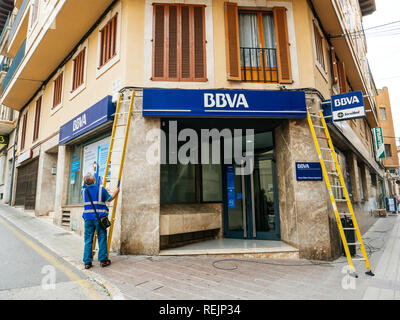 FELANITX, PALMA DE MALLORCA, SPAIN - MAY 10, 2018: Worker cleaning the facade insignia logotype of the Spanish BBVA bank during installation of fiber optic internet cable above entrance - Stock Photo