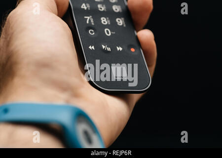 PARIS, FRANCE - JAN 26, 2018: Close-up of a modern man wearing a smartwatch and holding a TV remote control with Orange Telecom logotype in his left hand against a black background - Stock Photo