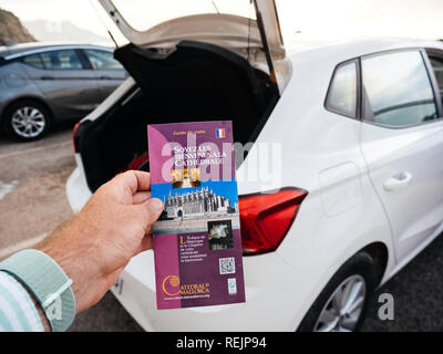 Port de Valldemosa, Palma de Malloca, Spain - May 10, 2018: Man holding point of view the touristic guide of the Santa Maria of Palma Cathedral in the parking near the open car trunk - Stock Photo