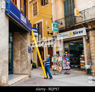 FELANITX, PALMA DE MALLORCA, SPAIN - MAY 10, 2018: Worker installing ladder to the facade insignia logotype of the Spanish BBVA bank while installing fiber optic internet cable above entrance - Stock Photo
